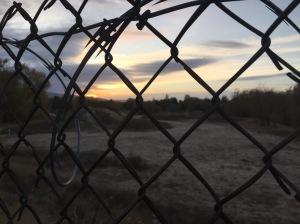 Sunrise behind razor wire